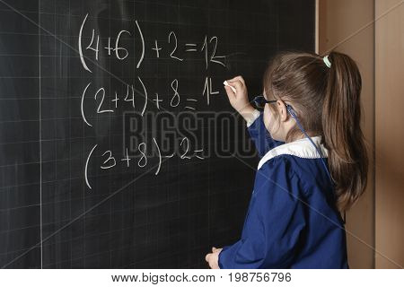 Italian elementary school girl first-grader solve mathematics examples. The student thinks and feels near the Board. Mathematical tasks.