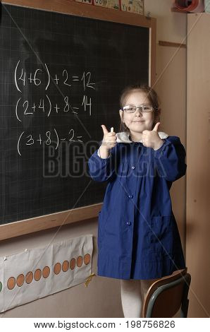 Happy smiling elementary school girl first-grader shows thub up on blackboard background. Educational and school concept