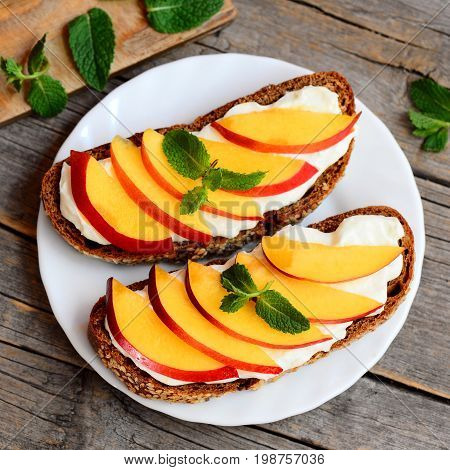 Nectarine cream cheese sandwiches on a plate and vintage wood background. Open sandwiches cooked from rye bread, fresh nectarines and soft cheese cream. Closeup