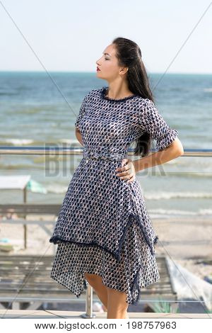 A charming woman posing on a glass terrace on a bright blue natural background. An elegant female in a saturated blue dress on an amazing vacation. A wonderful view on a noisy sea.