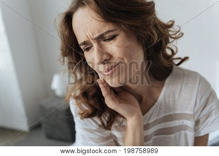 I need to visit a dentist. Upset gloomy young woman holding her cheek and suffering from pain while having a toothache