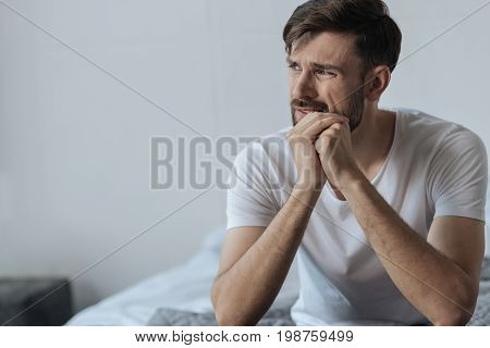 Hard times. Handsome nice bearded man holding his chin and feeling unhappy while thinking about his problems