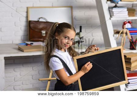 Girl With Happy Face Expression Near Desk With School Supplies