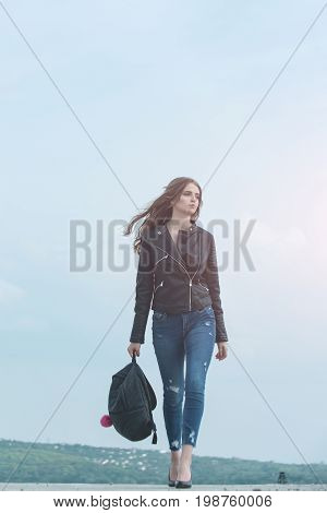 Girl in leather jacket. Sexy woman outdoor. Beauty and fashion. Fashion model on blue sky. Woman with long hair with backpack
