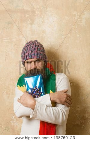 Man with long beard in colorful scarf. Holiday celebration and shopping. Hipster with present box in hat. Christmas and birthday. Guy with sad face and gift pack.