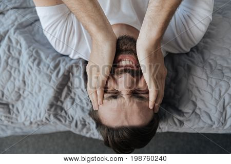 Bad times. Portrait of an unhappy sad depressed man lying on his bed and holding his face while having a failure