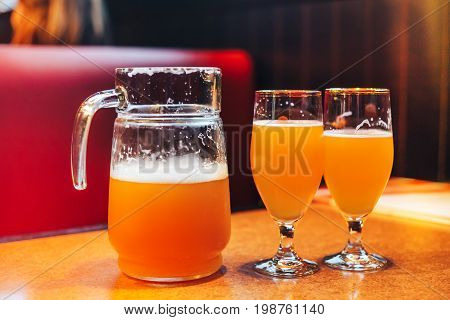 a pitcher and two glasses of beer in cafe