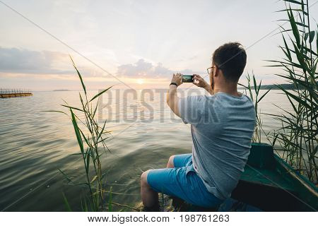 man taking picture on his phone of sunrise while sitting in old boat on the beach