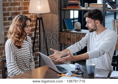 Having a quarrel. Unhappy angry handsome man sitting at the table and pointing at the laptop while having a quarrel with her