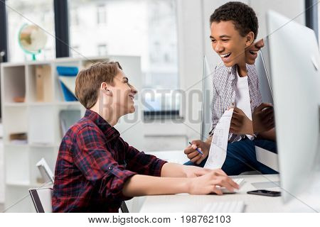 side view of multicultural teen boys studying together in class