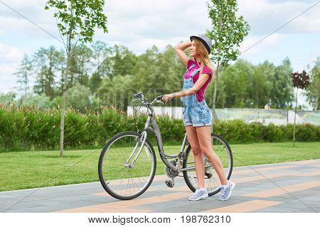 Full length shot of a young woman walking at the park with her bicycle nature outdoors recreation summer seasonal bicyclist riding sports activity concept.