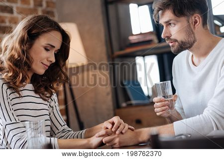 Care and support. Pleasant nice handsome man looking at his girlfriend and drinking water while holding her hand