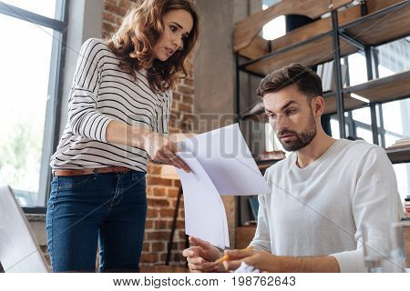 Explain this to me. Cheerless beautiful young woman holding documents and having questions to her boyfriend while being angry with him