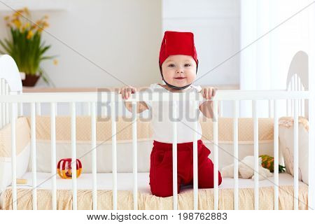 Funny Baby With Toy Basket As Helmet Are In His Cot