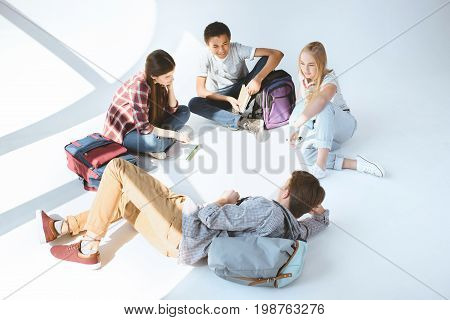 High Angle View Of Multicultural Group Of Students Resting After Classes Together Isolated On White