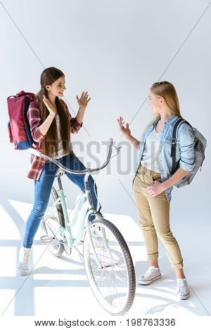 Caucasian Teenage Girls With Backpacks Talking And Looking At Each Other Isolated On White