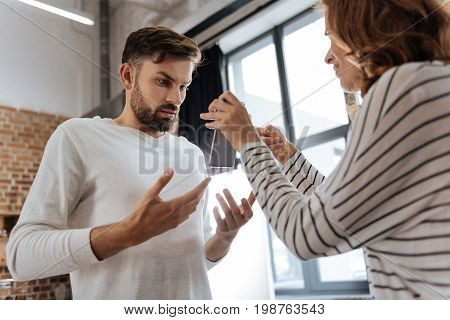 I did nothing. Nice handsome pleasant man standing opposite his girlfriend and looking at the smartphone screen while arguing with her