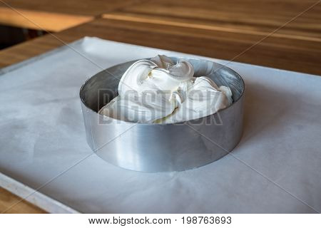 Form for baking cake with dough on baking tray with parchment paper. Dough for homemade cake in metal dish on the table