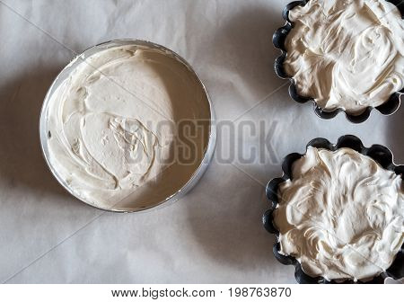 Forms For Baking Cakes With Dough On Baking Tray With Parchment Paper. Dough For Homemade Cakes In M