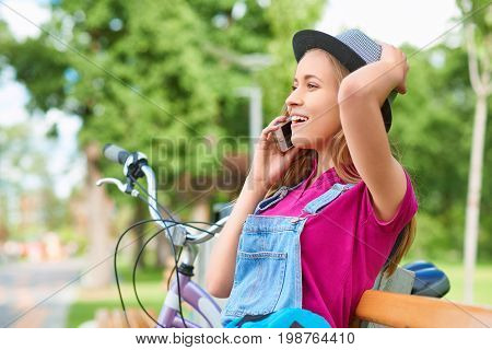 Gorgeous young woman looking excited while talking on the phone relaxing at the local park good news emotions happiness beauty recreation lifestyle carefree mobility technology carrier communication.