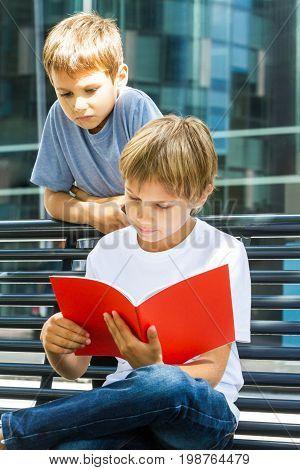 Schoolboys reading books. Children doing homework outdoors. Back to school concept.