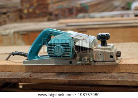 Electric planer on the wooden plank in carpentry workshop