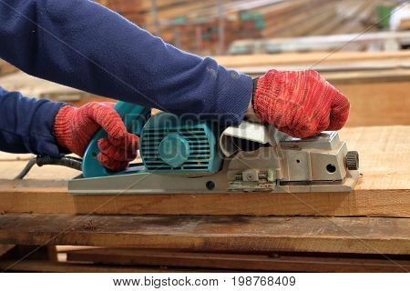 Hand of carpenter using electric planer with wooden plank in carpentry workshop