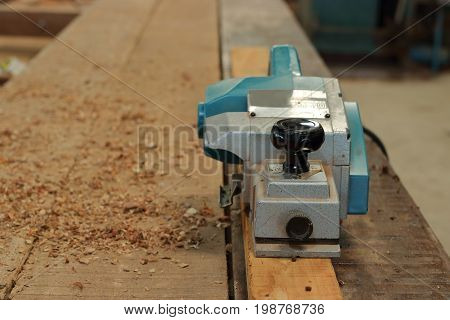 Electric planer with sawdust on the wood piece in carpentry workshop