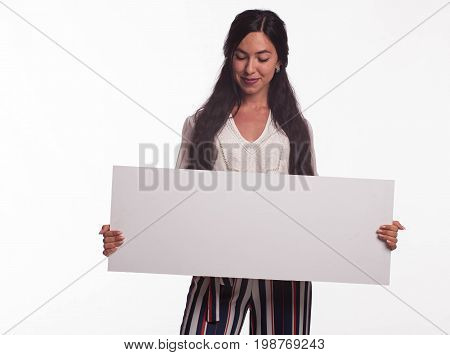 Young wistful woman portrait of a confident businesswoman showing presentation, pointing placard gray background. Ideal for banners, registration forms, presentation, landings, presenting concept.