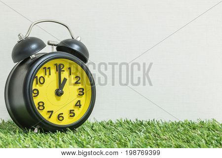 Closeup black and yellow alarm clock for decorate in 1 o'clock on green artificial grass floor and cream wallpaper textured background with copy space