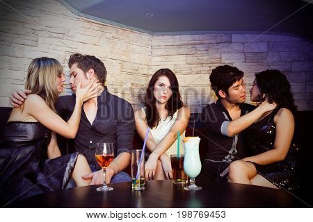 couples making out in a nightclub. a pretty but single woman is sitting between them, looking rather sad.