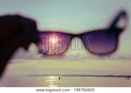 first-person view sunrise through sunglasses, hold glasses in hand