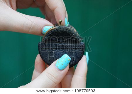Small black purse in the hands of a girl