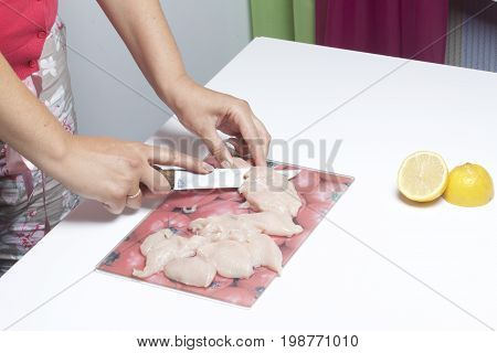 A Woman Chops A Chicken Fillet. Two Pieces Of Chicken Fillet. It Is Laid Out On A Cutting Board For