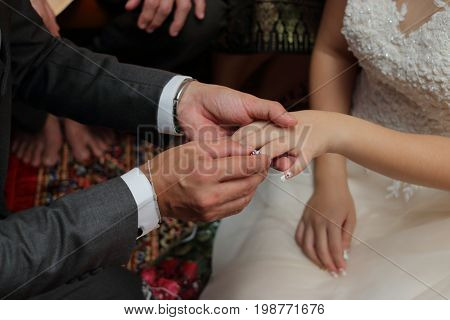 Groom put the wedding ring on bride's finger. Concept of marriage.