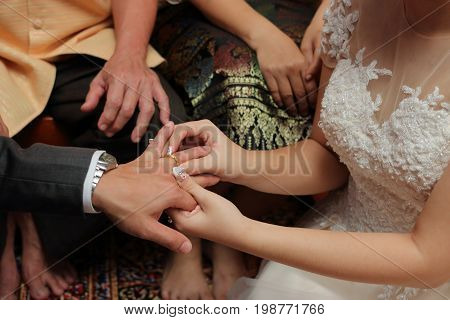 Bride put the wedding ring on groom's finger. Concept of marriage.