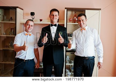 Handsome Groom Posing With His Groomsmen In The Room On The Wedding Day.