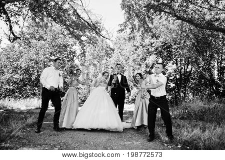 Beautiful Wedding Couple Walking And Having Fun With Groomsmen And Bridesmaids In The Park. Black An