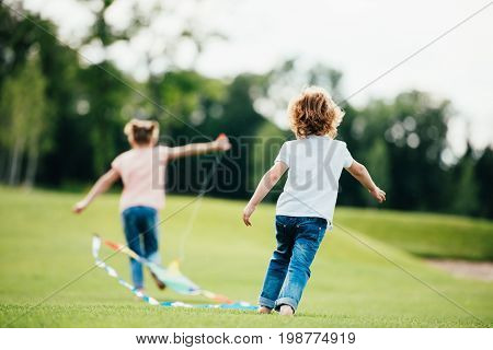 Back View Of Cute Little Boy And Girl Playing With Lite In Park
