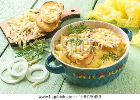 French onion gratin soup with cheese and toast. Delicious homemade soup in bowl ingredients on a board on a green wooden table