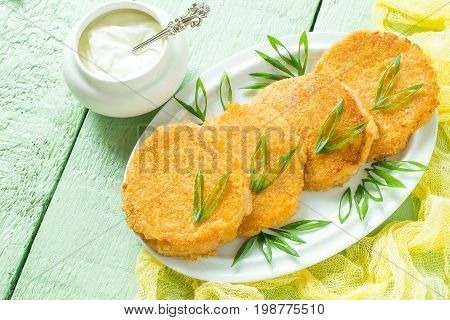 Tasty onion cutlet green onions and sour cream on green wooden table. The concept of dietary and vegetarian food. Healthy food