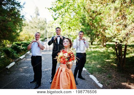 Handsome groom walking with his groomsmen and a bridesmaid in the park on a wedding day.