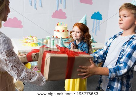 Side View Of Kids Presenting Gifts To Cute Happy Girl At Birthday Party