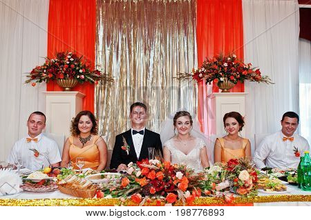 Awesome Wedding Couple Sitting At The Table With Groomsmen And Bridesmaids.