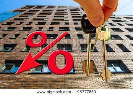 The percent symbol on a background of keys of the apartment and the facade of the new house .The concept of mortgage lending .