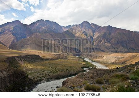 The view of the mountain range and floodplain river valley in Kyrgyzstan. Mountain river in Tien Shan stones rocks landscape stream water coast