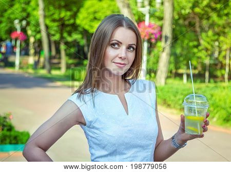 Beautiful young smiling woman, wearing elegant white dress, standing in the park, holding lemonade cocktail in a glass, refreshing in a hot summer day