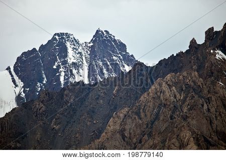 Views of mountain peaks ridges and gorges of the Tien-Shan mountains in the clouds and the clouds. Kyrgyzstan. Bad weather in the mountains.