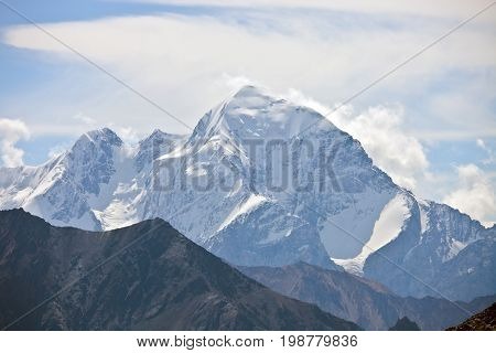 The mountain top with steep slopes cliffs glaciers in the Tien Shan in the autumn. Kyrgyzstan