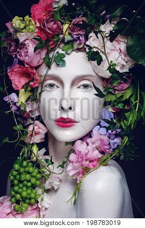 Beautiful young pale white woman with different flowers on head. Flower queen. Beauty shot on black background.